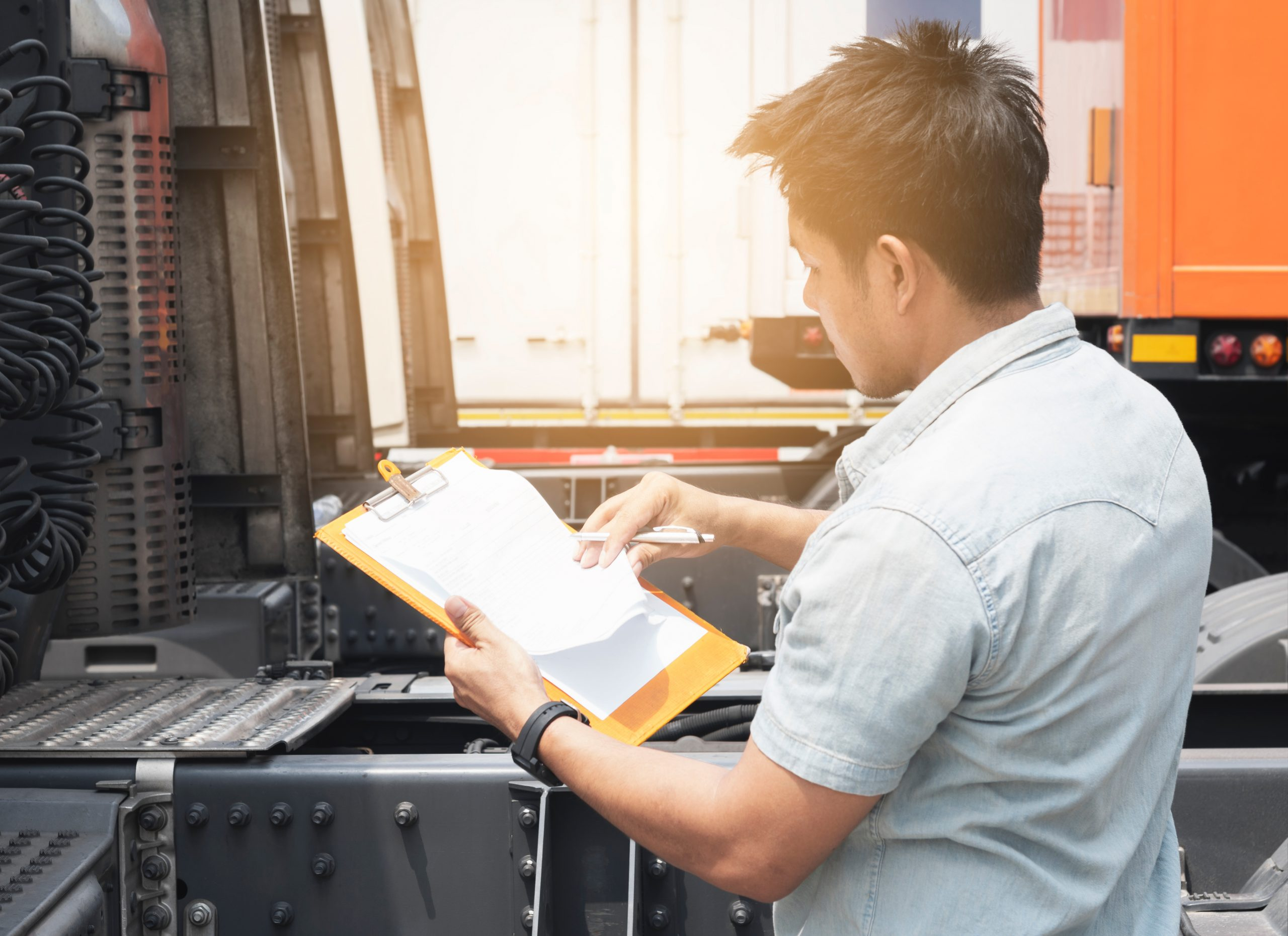 Truck driver holding clipboard inspecting safety vehicle maintenance checklist a truck trailer, Road freight industry logistics